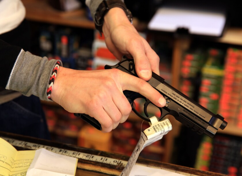 A gun shop employee in Tinley Park, Ill., outside Chicago, shows a Beretta 9mm handgun in 2014.