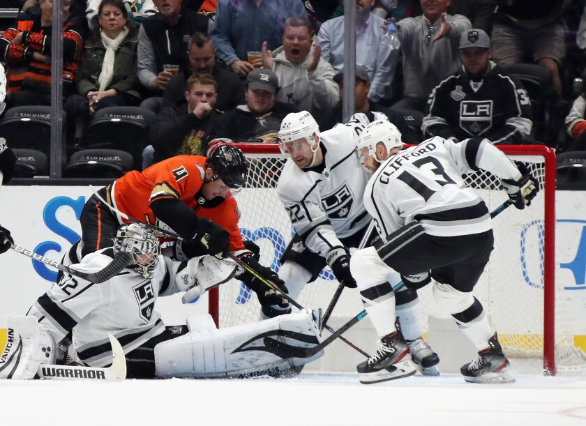 Kings goaltender Jonathan Quick and teammates Trevor Lewis and Kyle Clifford try to stop Ducks defenseman Cam Fowler from scoring.