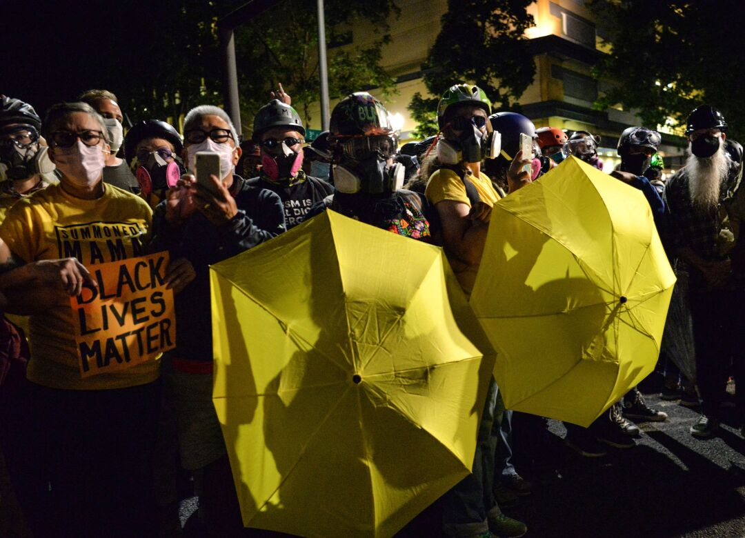 Protesters carry umbrellas as they gather at the Mark O. Hatfield Courthouse in Portland, Ore.