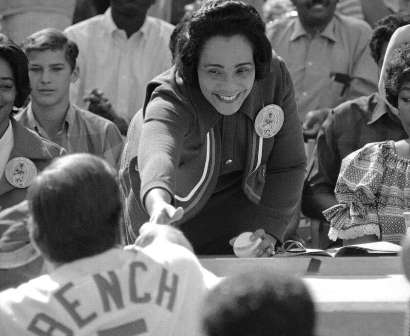 Coretta Scott King, widow of the Rev. Martin Luther King Jr., reaches out to shake hands with catcher Johnny Bench of the Cincinnati Reds, who caught her first pitch thrown at Dodger Stadium in Los Angeles of March 28, 1970, for the East-West All-star game