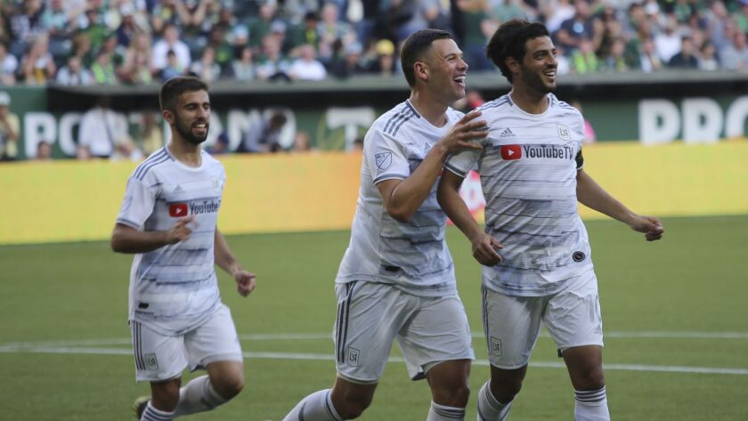 Los Angeles FC's Carlos Vela, right, smiles after a goal during an MLS soccer match against the Port