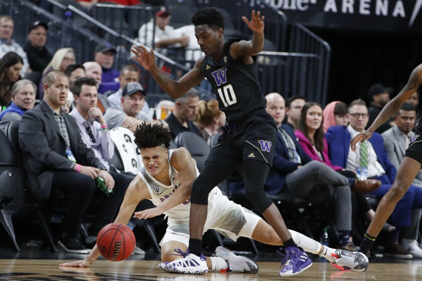 Arizona's Josh Green, left, and Washington's Elijah Hardy (10) battle for the ball during the first half of the Pac-12 men's tournament on Wednesday in Las Vegas.