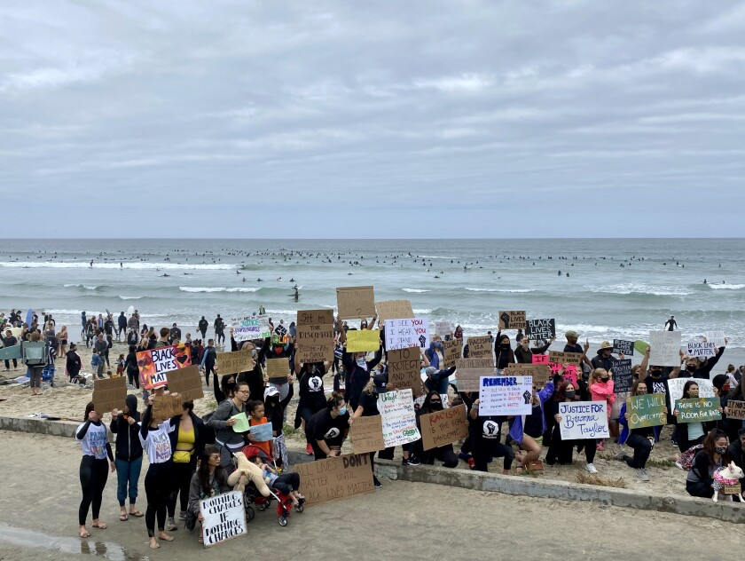 Protesters gather with signs during the Paddle for Peace at Tourmaline as surfers go in the ocean to honor George Floyd.