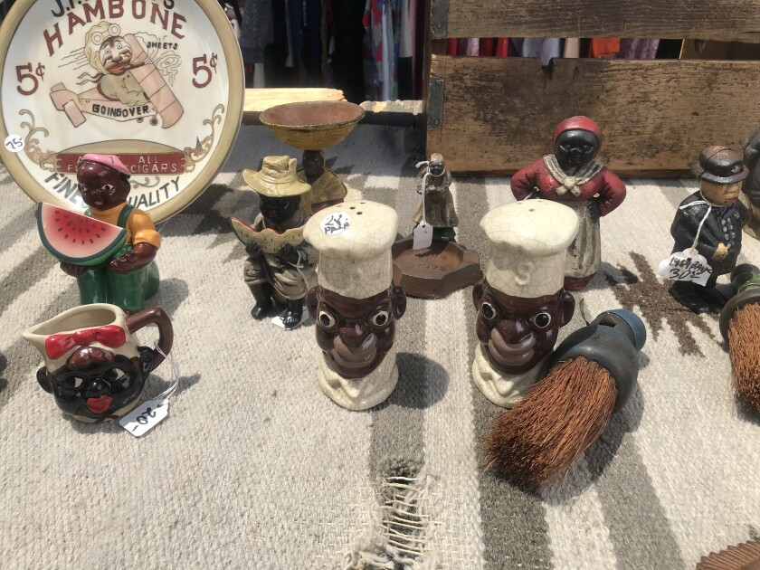 About a dozen anti-Black figurines sit on a table including saltshakers, a mug and plate.