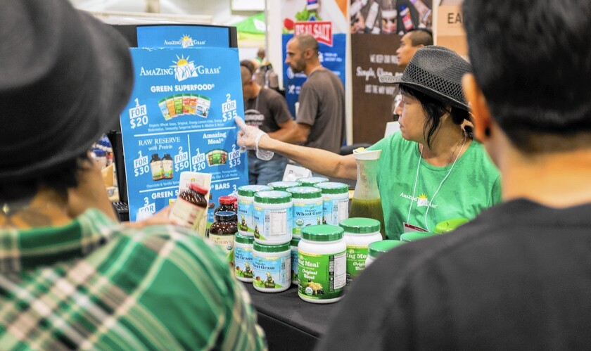 People visit the Amazing Grass booth at the 2015 Green Festival at the Los Angeles Convention Center. Under a settlement the state attorney general's office announced, the Newport Beach-based company will pay $213,167 in penalties for selling nutrition products with excessive levels of lead and cadmium.