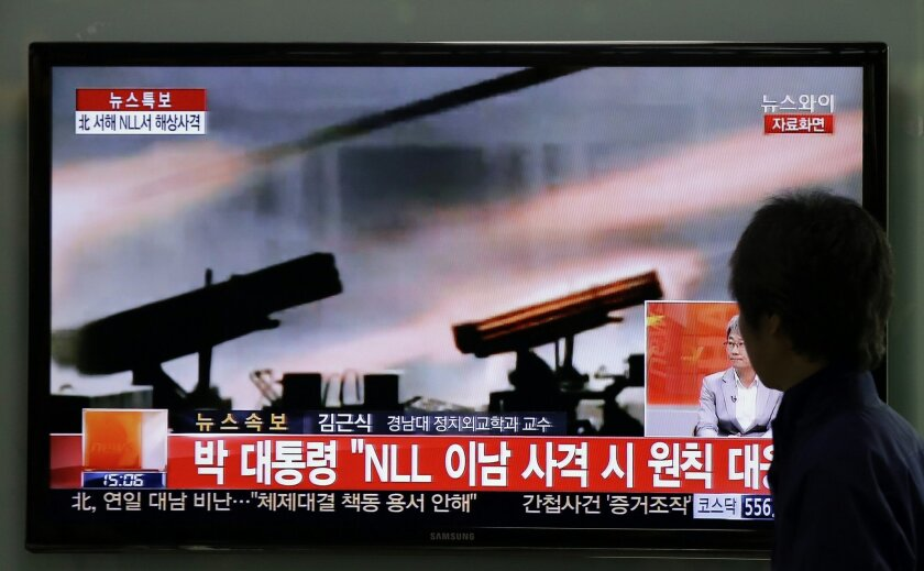 A man watches a television news program reporting about North Korea's live-fire artillery drills at a Seoul train station in Seoul, South Korea, Tuesday, April 29, 2014. North Korea conducted live-fire artillery drills Tuesday near the countries' disputed western sea boundary, South Korean military officials said, in a possible indication of rising frustration in Pyongyang as it unsuccessfully pushes for outside aid. (AP Photo/Lee Jin-man)