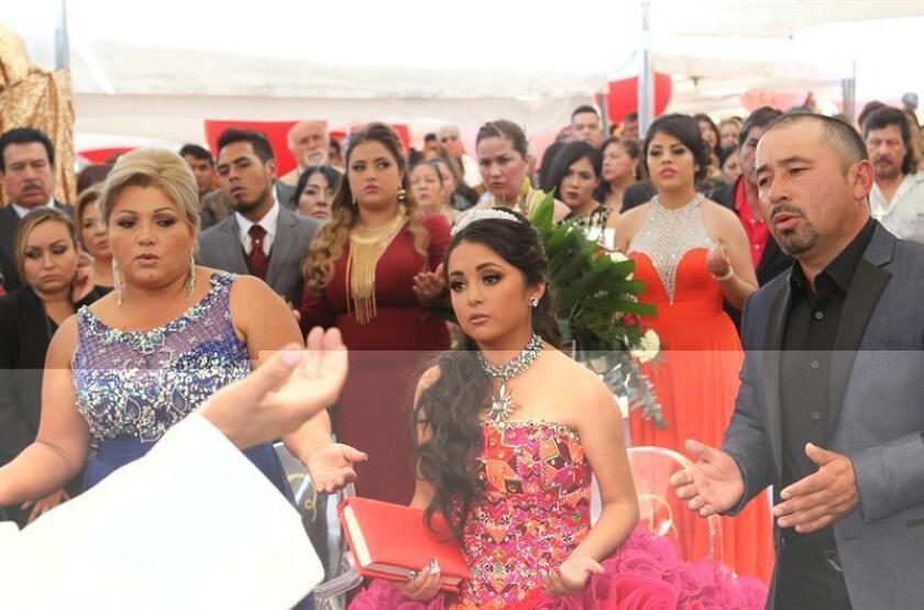 La joven mexicana Rubí (c) junto a sus padres en una misa en el marco de su fiesta de 15 años hoy, lunes 26 de diciembre de 2016, en La Joya (México). El cumpleaños número quince de la mexicana Rubí, un evento que pasó de ser algo local a convertirse en un fenómeno mediático en México y el extranjero gracias a las redes sociales, se mantiene como tendencia en estas plataformas virtuales el día en que se realiza la fiesta. EFE