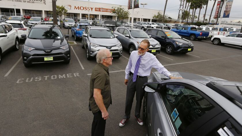 Salesman Rick Kitsmiller, right, shows off a Toyota Rav4 to customer Eric Jones at Mossy Toyota in Pacific Beach in November 2017. A recent study reports that car owners in San Diego ranked sixth in the nation when it comes to keeping their vehicles for 15 years or longer.