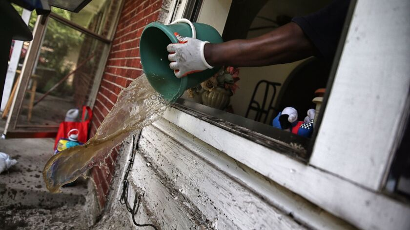 James Jackson scoops water, a bucket at a time, from his family home in Houston.