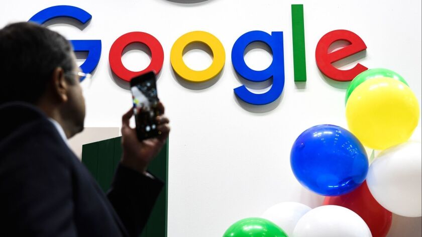 A man snaps a picture of the Google logo May 16 at the VivaTech startups and innovation fair in Paris.