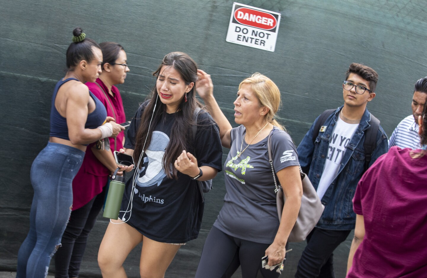A student cries as her mother picks her up from the reunion gate at CHAMPS Charter High School of the Arts after a shooting near the Van Nuys campus.