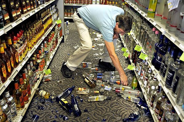Ben Gayle picks up broken glass and liquor bottles at an ABC store in Stafford, Va., after an earthquake in August 2011.