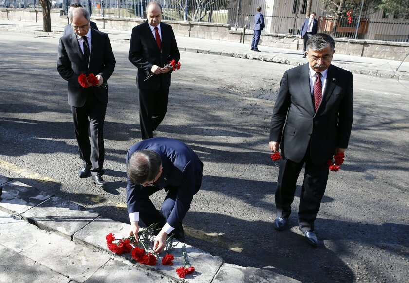 Turkish Prime Minister Ahmet Davutoglu lays carnations at the Wednesday explosion site in Ankara, Turkey, Friday, Feb. 19, 2016.  Interior Minister Efkan Ala, left, and Defense Minister Ismet Yilmaz, right, prepare to lay their flowers. (AP Photo/Umit Bektas, Pool)