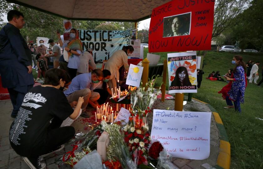 Activistas colocan velas y flores junto a carteles con fotos de Noor Mukadam, una mujer de clase alta que fue golpeada y decapitada recientemente en Islamabad. Foto del 25 de julio del 2021. La violencia contra la mujer está en aumento en Pakistán, junto con la influencia de la derecha religiosa, según activistas. (AP Photo/Anjum Naveed)