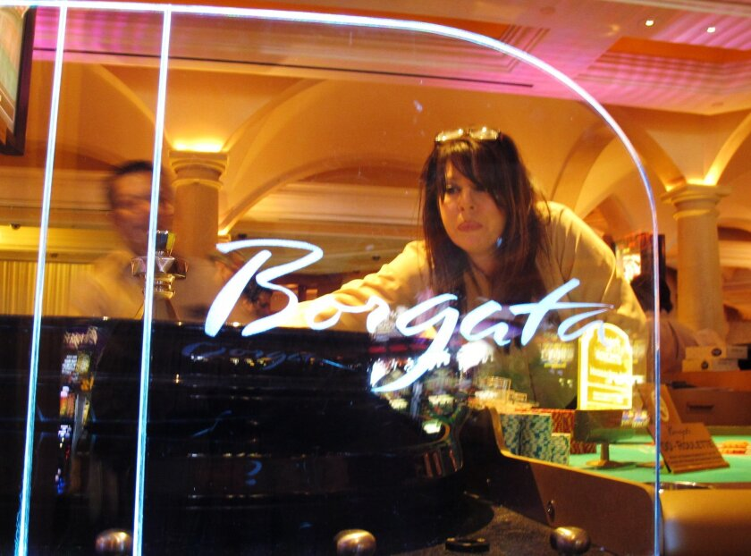 In this June 26, 2013 photo, dealer Sydney Vasaturo conducts a game of roulette at the Borgata casino in Atlantic City, N.J. On Tuesday, May 31, 2016, Boyd Gaming announced it is selling its 50 percent ownership stake in the Borgata to MGM Resorts International, the company that owns the other half