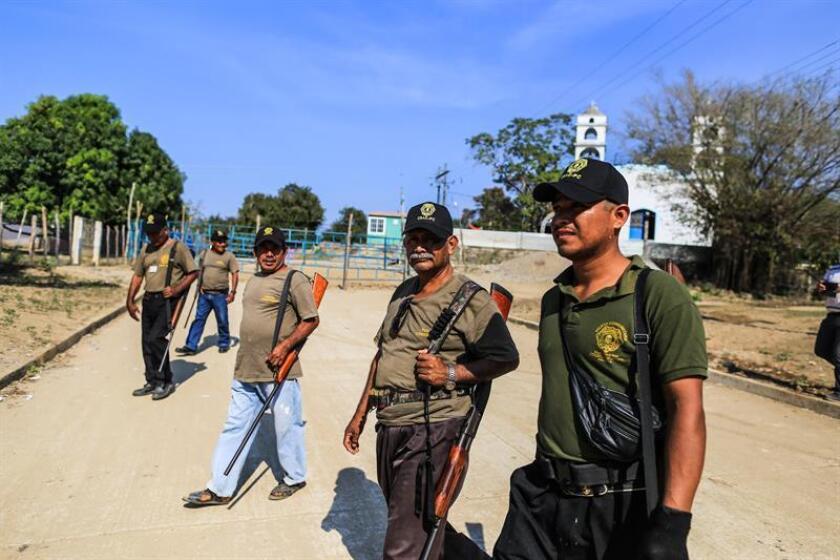 Guardias comunitarios participan hoy, en el acto de conmemoración del aniversario del enfrentamiento que cobró la vida de 11 personas, en el estado de Guerrero (México). EFE