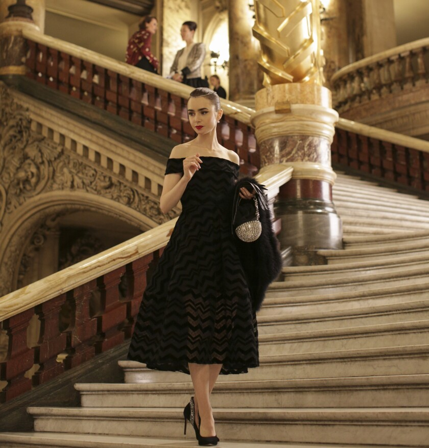 Lily Collins wears a black dress and high heels standing on a staircase