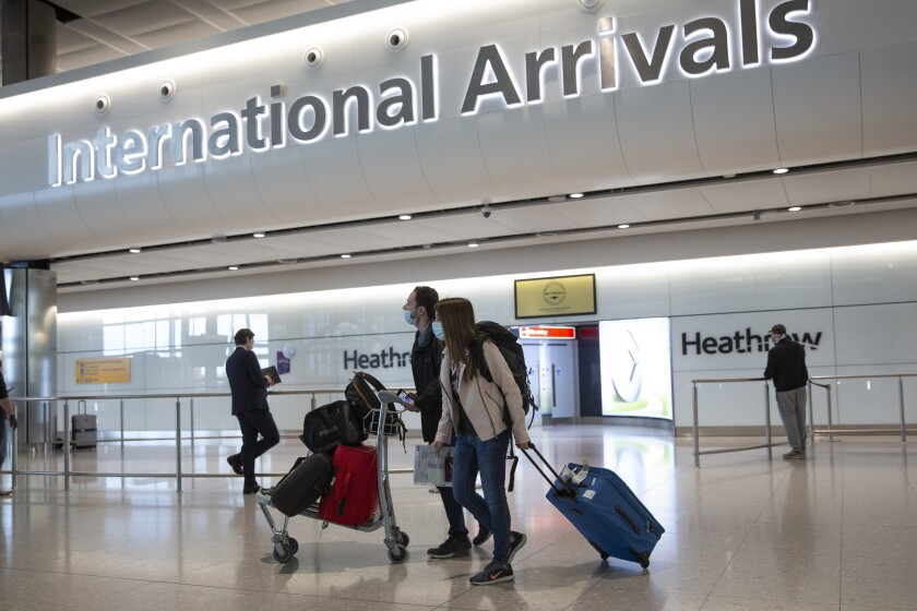 FILE - In this file photo dated Monday, June 8, 2020, passengers wearing face masks arrive at London's Heathrow Airport. Britain's airports are much less busy than they would otherwise be in any other year, but the traditional British summer getaway to the sun-soaked beaches is set to pick up steam as quarantine restrictions are removed to dozens of countries, Friday July 10, 2020. (AP Photo/Matt Dunham, File)