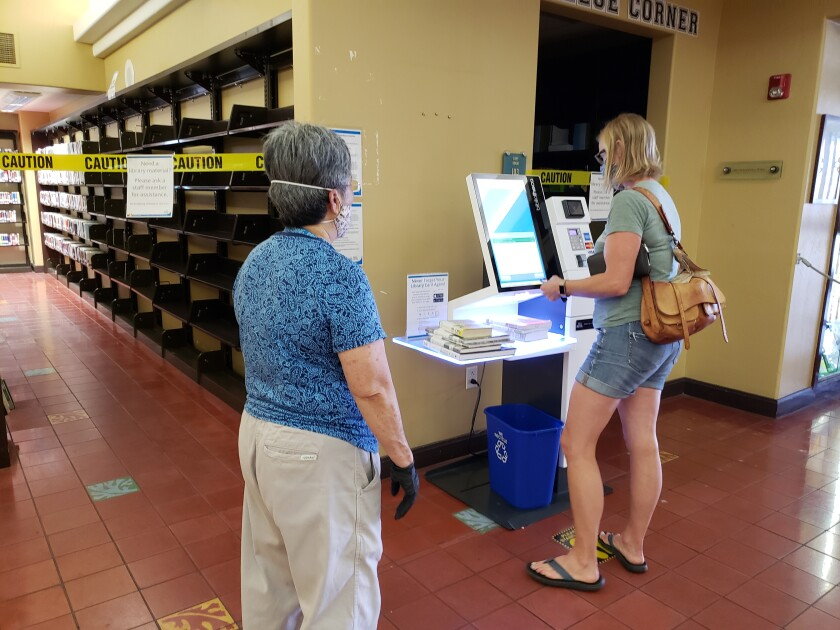 La Jolla/Riford Library patron Amanda Notman gets help from a librarian in using the self-checkout kiosk Oct. 5.