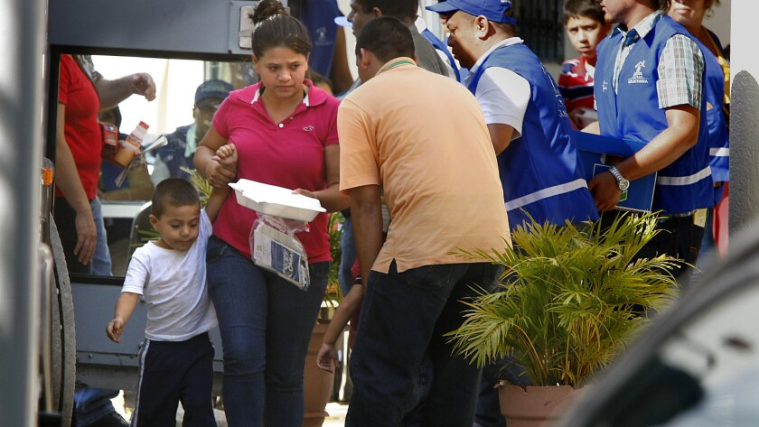 A mother from the first planeload of Honduran women and children who were deported from the U.S. leads her son toward a bus at the Center for Returned Migrants in San Pedro Sula, Honduras, on Monday.