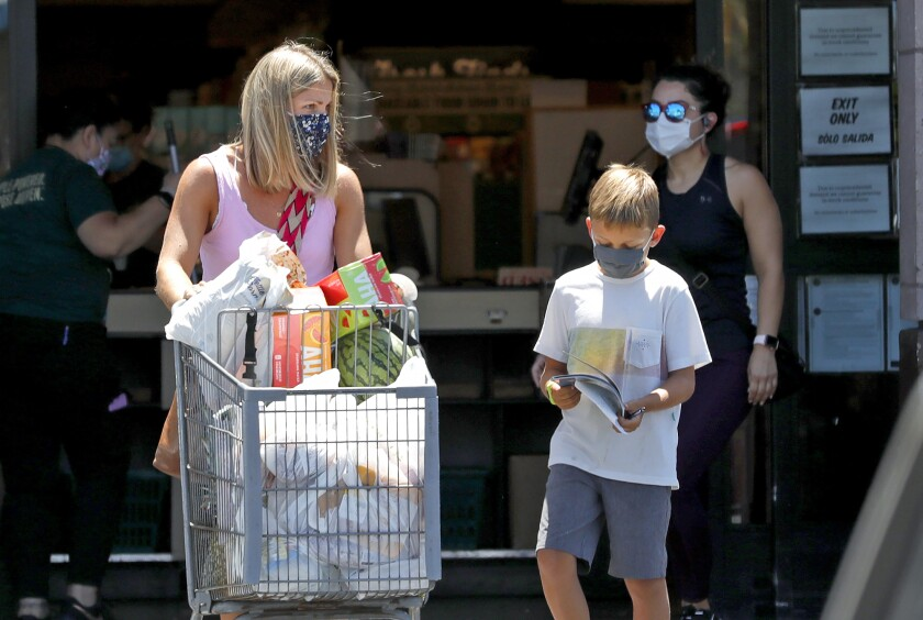 Shoppers walk out of a Sprouts market in Costa Mesa on Monday.