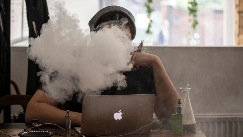 A student uses a vaping device.