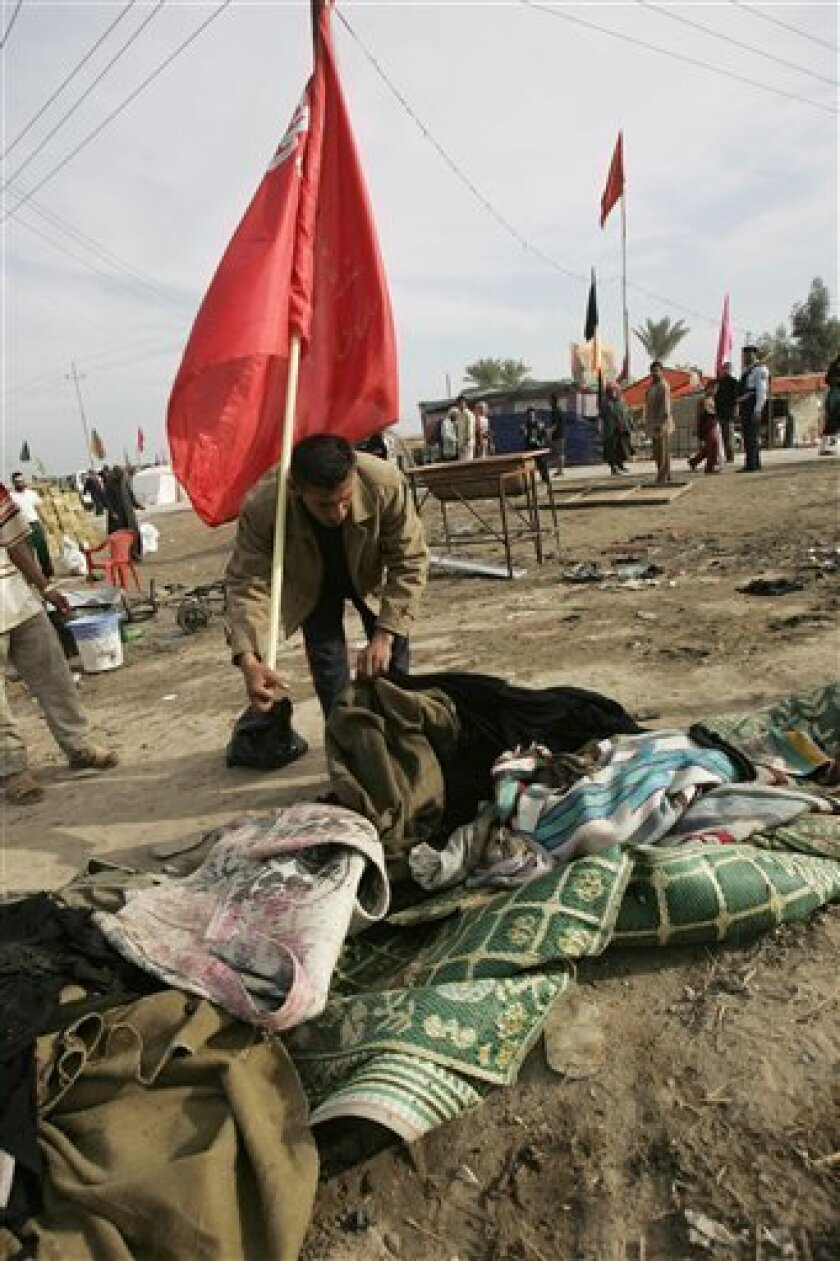 A pilgrim inspects the site of a suicide bombing that killed 40 people near Musayyib, about 40 miles (60 kilometers) south of Baghdad, Friday, Feb. 13, 2009. A female suicide bomber struck a tent filled with women and children resting during a Shiite pilgrimage near Musayyib, killing 40 people and wounding about 80 in the deadliest of three straight days of attacks against Shiite worshippers. (AP Photo/Alaa al-Marjani)