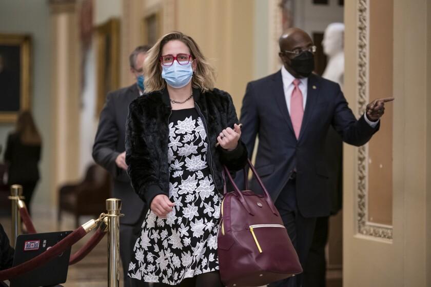 Sens. Kyrsten Sinema and Raphael Warnock walk through the Capitol