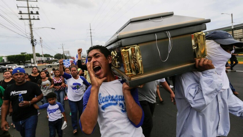 Nicaragua's Roman Catholic Church defended students against government repression during last year's protests. Friends and relatives carry a coffin with the body of a student shot during clashes with police in a church in Managua in July 2018.