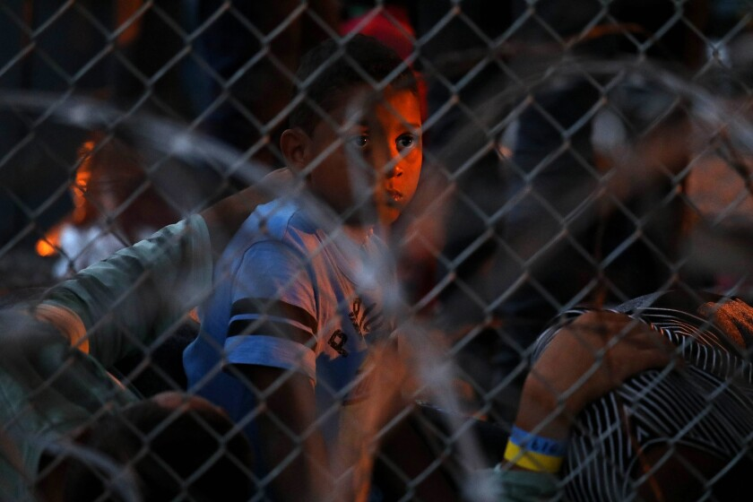 Asylum seekers are held in a temporary transition area under the Paso Del Norte bridge in El Paso on March 28, 2019.