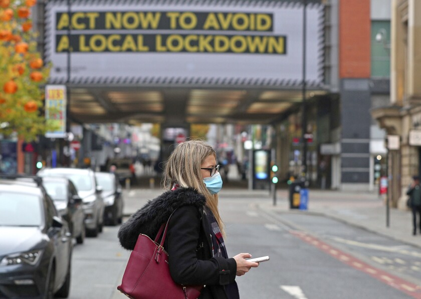A woman wearing a mask walks in Manchester, England, on Oct. 19, 2020.