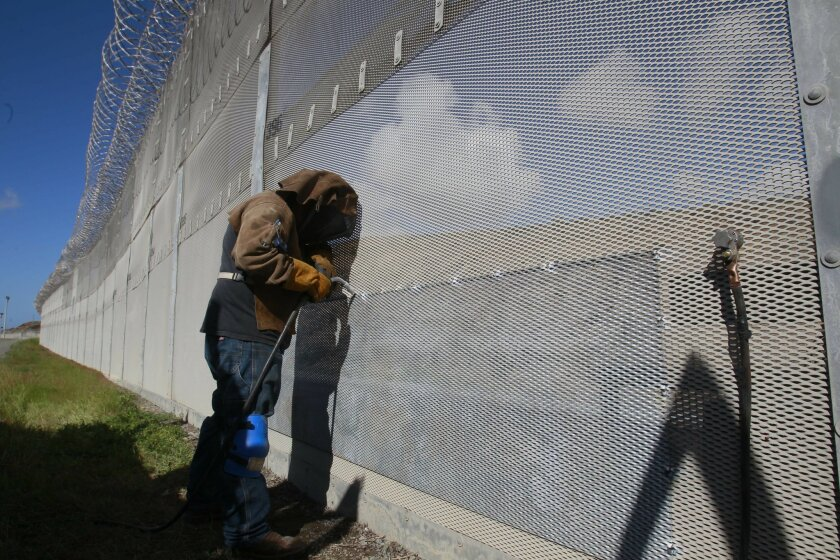 A welder working for the U.S. government closed up a patch in the fence from a crossing attempt.