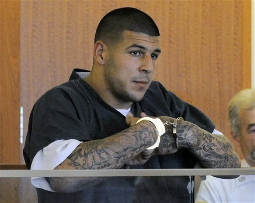 FILE - Former New England Patriots football tight end Aaron Hernandez stands during a bail hearing in Fall River Superior Court in this June 27, 2013 file photo taken in Fall River, Mass. An associate of former New England Patriots tight end Aaron Hernandez said he was told Hernandez fired the shots that resulted in the death of a semi-pro football player, according to documents filed in Florida. The records say Hernandez associate Carlos Ortiz told Massachusetts investigators that another man,