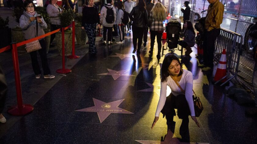 LOS ANGELES, CA - FEBRUARY 28: People pose for pictures with stars on along Hollywood blvd., on Febr
