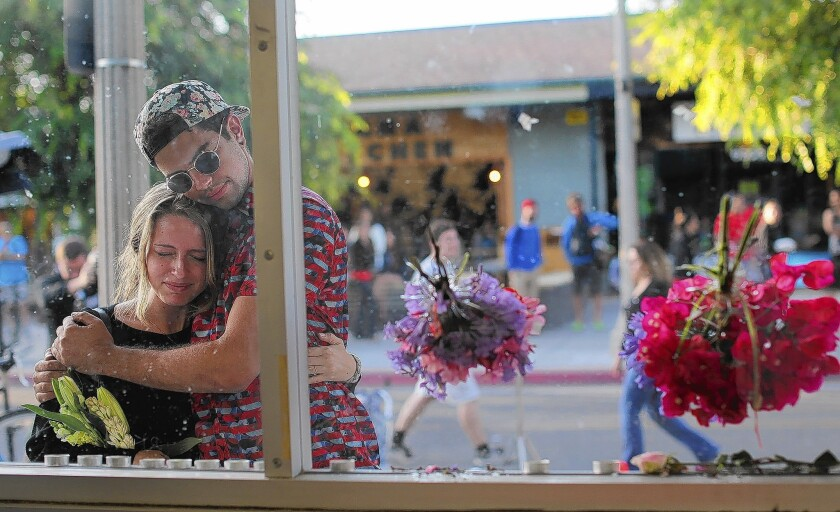 UCSB student Connor London gets a hug from fellow student Noel Peake after placing memorial flowers in the bullet holes in the front glass of the I.V. Deli Mart in Isla Vista.