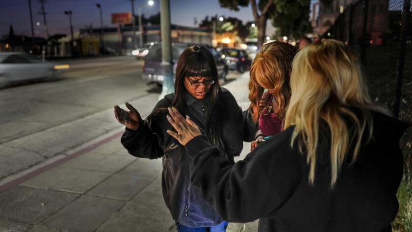 Members of Victory Outreach church Tamika Bonner, left, and Toni Dominguez, right, pray with with a woman on International Boulevard in Oakland. The church group helps women working as prostitutes with shelter and other social services.