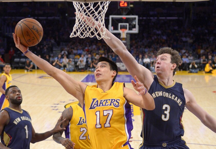 Lakers guard Jeremy Lin shoots next to New Orleans center Omer Asik on April 1.