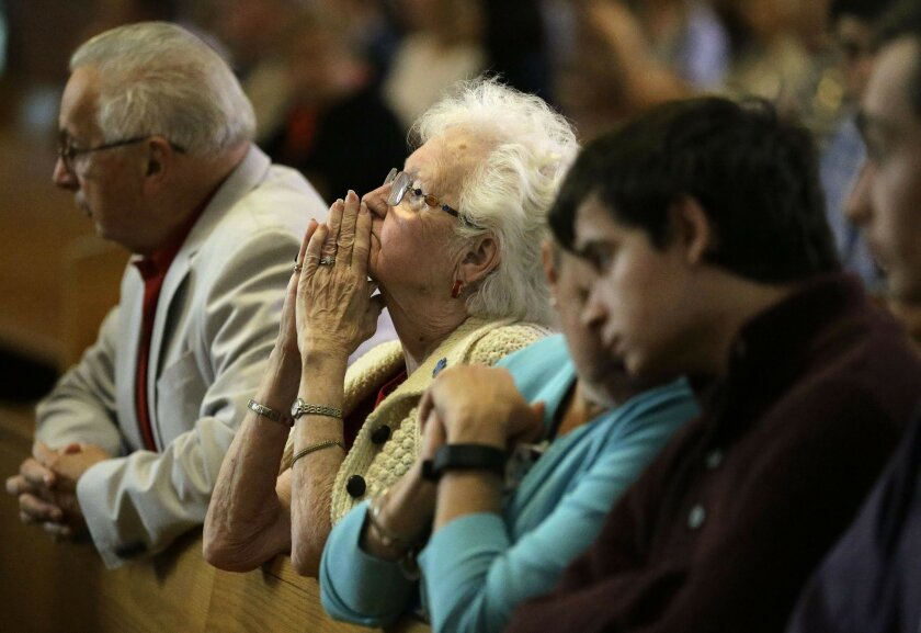 Parishioner Joanmarie Gorman, of Scituate, Mass., center, places her hands together during a planned final service at St. Frances X. Cabrini Church, Sunday, May 29, 2016, in Scituate. For more than 11 years, a core group of about 100 die-hard parishioners at the church have kept their parish open b