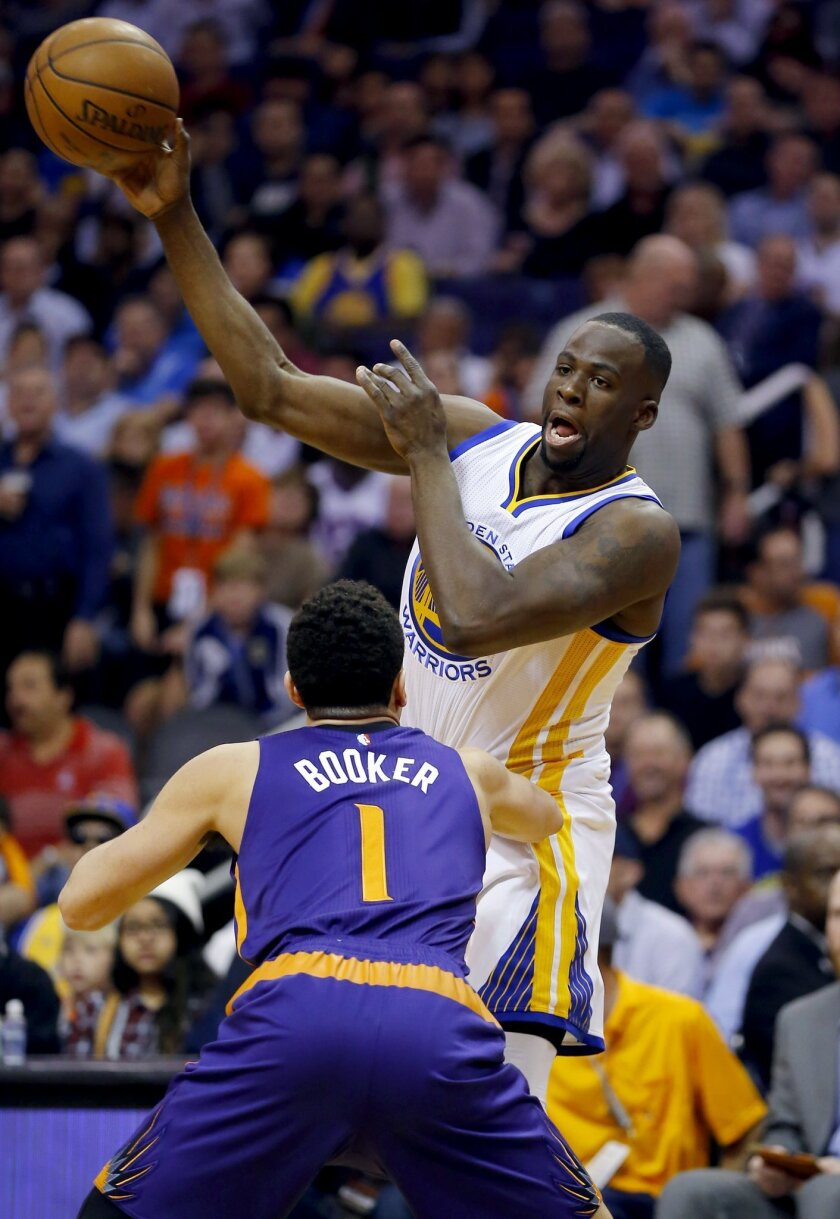 Golden State Warriors' Draymond Green passes over Phoenix Suns' Devin Booker (1) during the first half of an NBA basketball game, Wednesday, Feb. 10, 2016, in Phoenix. (AP Photo/Matt York)