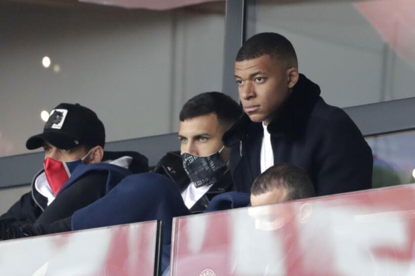 El delantero del PSG Kylian Mbappé (derecha) observa el partido contra Lens por la liga francesa, el sábado 1 de mayo de 2021, en el estadio Parc des Princes. (AP Foto/Thibault Camus)
