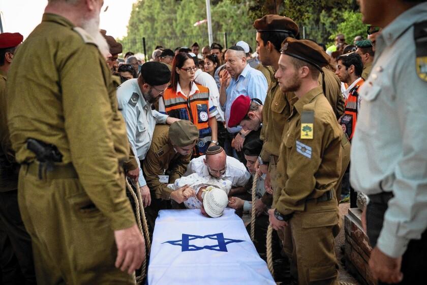The grandmother of Israeli soldier Jordan Bensimon cries over his casket Tuesday.