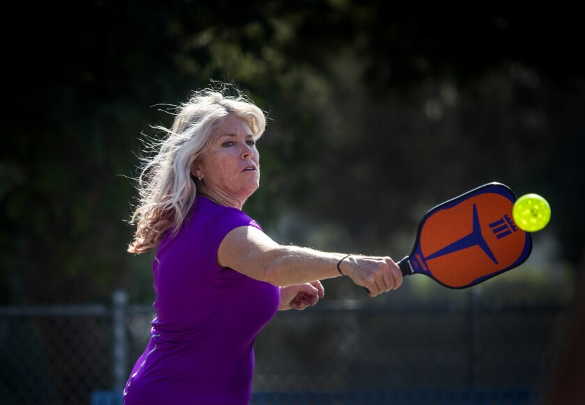 Susan Joyner makes a backhand return while playing pickleball at the Worthy Park courts in Huntington Beach.