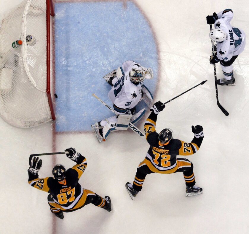 The overtime goal by Pittsburgh Penguins' Conor Sheary, not seen, bounces out of the net behind San Jose Sharks goalie Martin Jones (31) with Marc-Edouard Vlasic (44) defending as Penguins' Sidney Crosby (87) and Patric Hornqvist (72) begin to celebrate in Game 2 of the NHL hockey Stanley Cup Final
