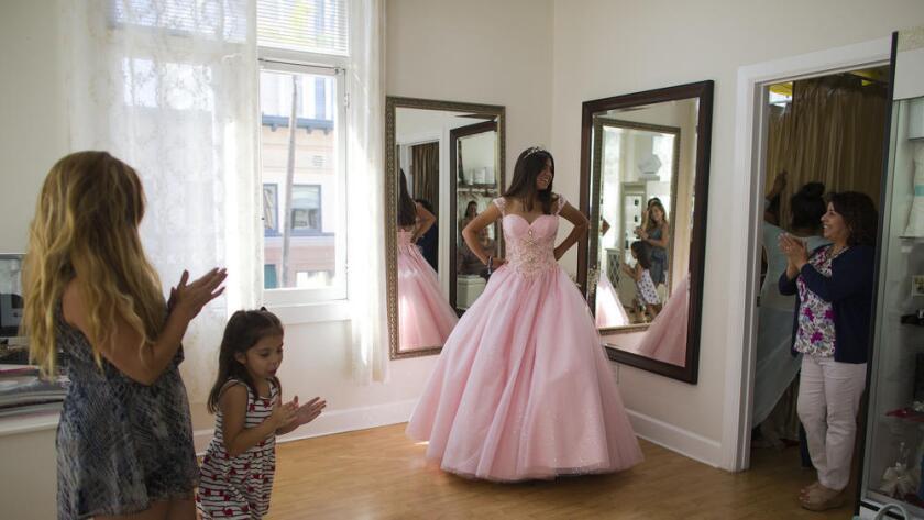 Natalie Anaya, de 14 años, es aplaudida por su madre Ana Pérez, su hermana Isabella Pérez y Lilia Cerpas, dueña del negocio de vestidos de quinceañera, en Santa Ana. (Gina Ferazzi / Los Angeles Times)