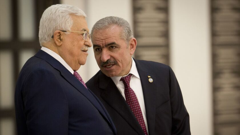 Palestinian Prime Minister Mohammad Ishtayeh, right, talks with Palestinian President Mahmoud Abbas
