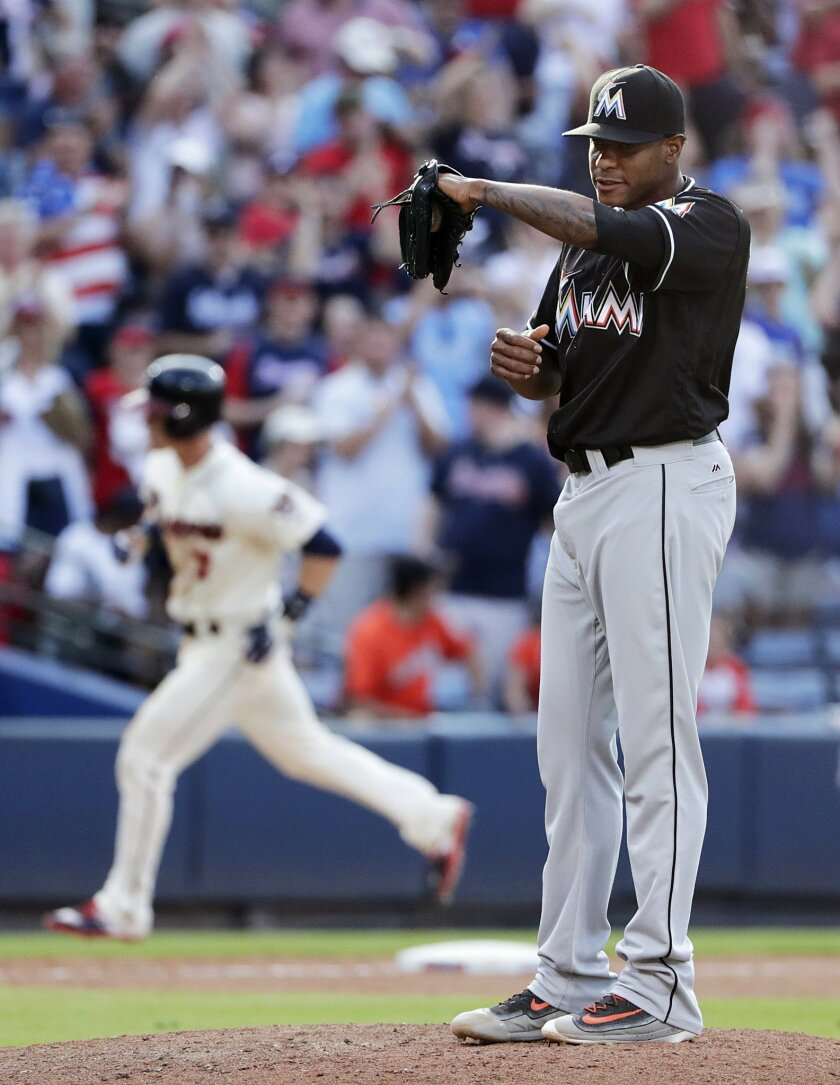 Miami Marlins relief pitcher Edwin Jackson stands on the mound after giving up a three-run home run to Atlanta Braves' Gordon Beckham, rear, in the seventh inning of a baseball game, Saturday, May 28, 2016, in Atlanta. (AP Photo/David Goldman)