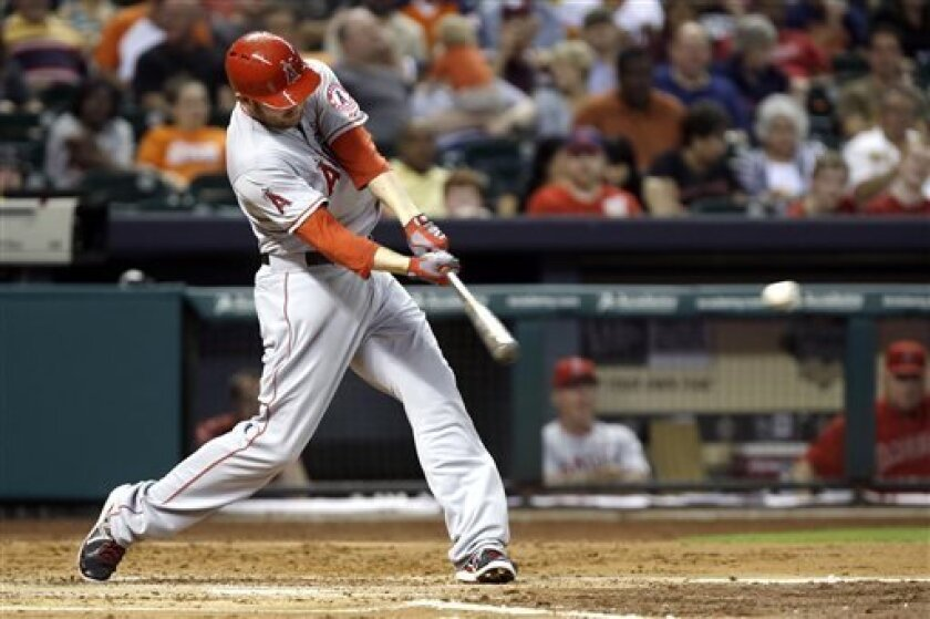 Los Angeles Angels' Mark Trumbo connects for a two-run triple against the Houston Astros in the third inning of a baseball game Friday, Sept. 13, 2013, in Houston. (AP Photo/Pat Sullivan)