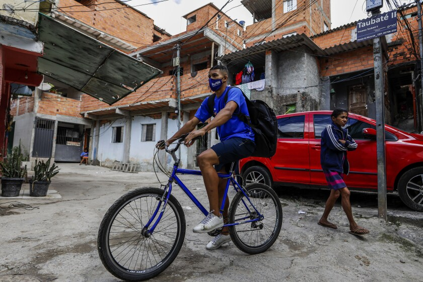 Logistics company Favela Brasil Xpress deliveryman Jonathan Arcanjo, cycles through alleys to deliver orders in the Paraisopolis favela of Sao Paulo, Brazil, Tuesday, Aug. 31, 2021, amid the COVID-19 pandemic. Favela Brasil Xpress, a startup created six months ago, reached the milestone of 100,000 packages delivered in areas that are not properly served by the postal service or by traditional transport and delivery companies, while ensuring the arrival of food, medicine and home supplies to people in the community. (AP Photo/Marcelo Chello)