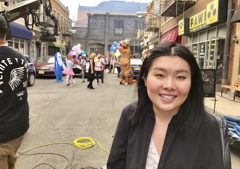 """In this image provided by Kaitlyn Yang, Yang poses for a photo on the set of """"Polaris Primetime."""" Women of color who work behind the camera in fields including writing and visual effects are finding career support, including from the Television Academy Foundation and its internships. But four former interns say the industry must do more to foster diversity. (Kaitlyn Yang via AP)"""
