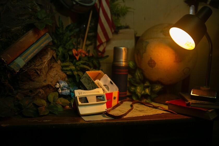 Una vista maestra, globo terráqueo, libros y otros artículos en un escritorio iluminado por una pequeña lámpara